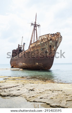 Ship wreck surrounded by sea waves on moody Selinitsa beach, Gytheio, Greece