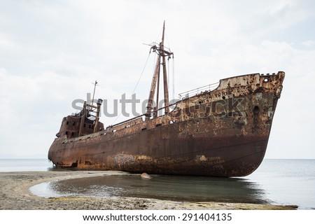 Ship wreck surrounded by sea waves on moody Selinitsa beach, Gytheio, Greece - stock photo