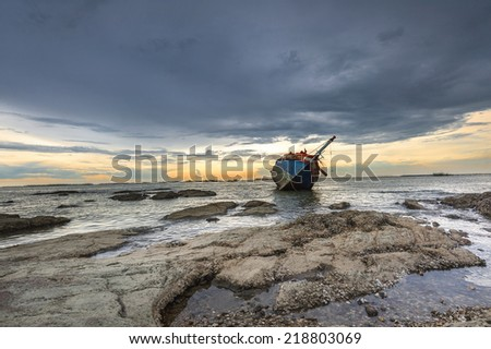 ship wrecked  at sunset - stock photo