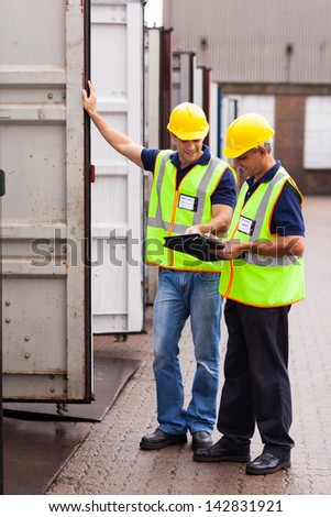 shipping company workers recording containers at the warehouse - stock photo