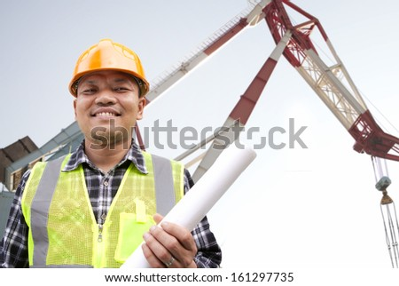Shipping engineer with blueprint on the deck of a large industrial