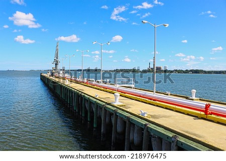 Shipping fuel delivery lines leading out on and old wooden pier into the York river in Yorktown Virginia for coast guard, Naval and other shipping vessel fueling needs. - stock photo