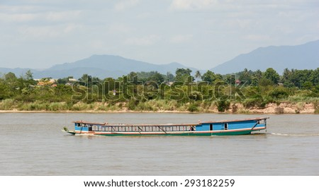 Shipping Lao boat carry goods from border of Myanmar and Lao on The Mae khong river in Chiangsaen ,Chiangrai Thailand - stock photo
