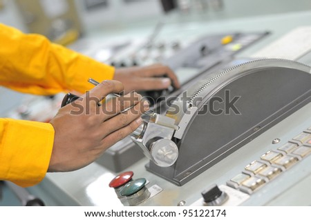 Shipping officer controlling shipping vessel at engine room. - stock photo
