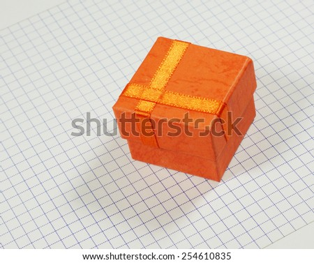 Shipping orange box on the notebook grid background