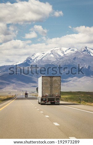 shipping truck on a highway in nevada with spring snow on large tall mountains in the background - stock photo