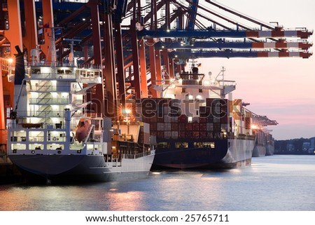 ships in harbor - giant freighters in port being loaded with containers, setting sun - stock photo