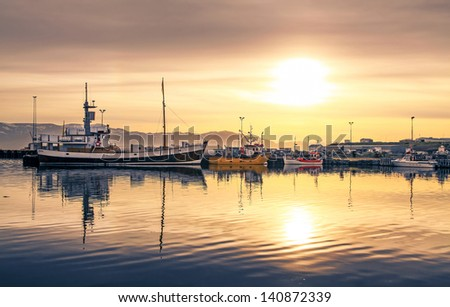 Ships lying in the harbor of Husavik at sunset, Iceland - stock photo