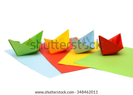 Ships origami. Paper boats on colored sheets. Colorful figures. Transport origami. - stock photo