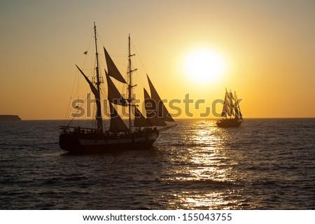 Ships sailing into the sunset at Oia, Santorini, Greece - stock photo