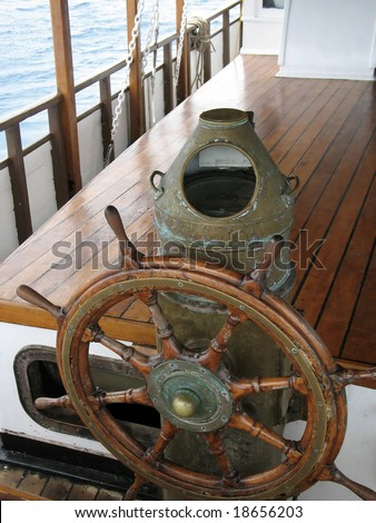 Ships wheel, Brass Binnacle & Compass with teak decking and sea as background