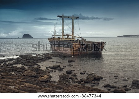 Shipwreck on reef and oil leaking - stock photo