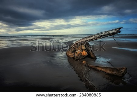 Shipwreck on the sandy beach  - stock photo