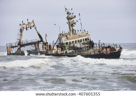 Shipwreck with cormorants on Skeleton Coast near Swakopmund, Namibia, Africa. - stock photo