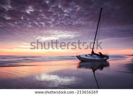 Shipwrecked boat on the Cape Hatteras National Seashore at sunrise in North Carolina Outer Banks. - stock photo
