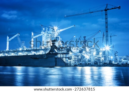 Shipyard at work, ship repair. Industrial machinery, cranes. Transport, freight concept - stock photo