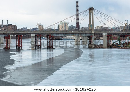 Shipyard with big chimney and cranes on the riverbank - stock photo