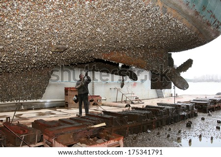 Shipyard worker cleans the ship stuya water from vegetation and mussels - stock photo