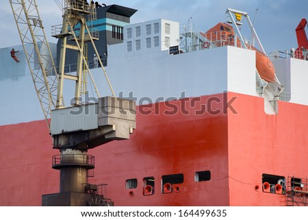 shipyard worker painting a ship under construction on drydock in Gdansk Shipyard. - stock photo