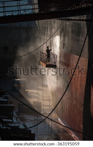 Shipyard worker power washing a ship on dry dock. - stock photo