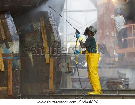 shipyard worker powerwashing a ship on drydock - stock photo
