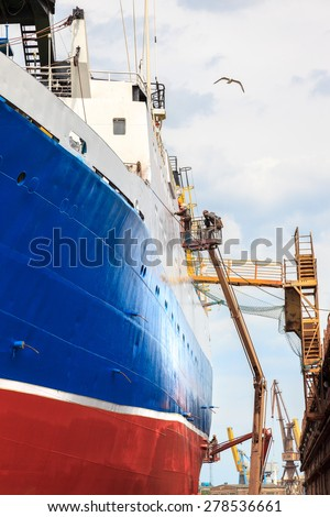 Shipyard worker to clean ship after painting.  - stock photo