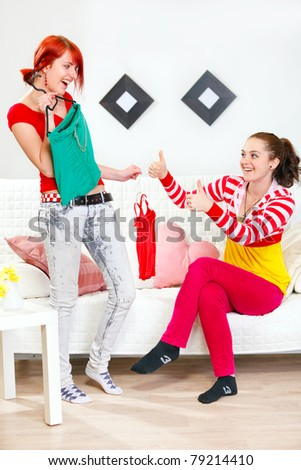 Shirt approved. Cheerful young girl helping choose clothes her girlfriend - stock photo