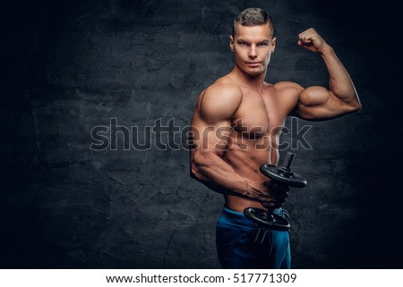 Shirtless abdominal suntanned young male fitness model holds dumbbell on grey background.
