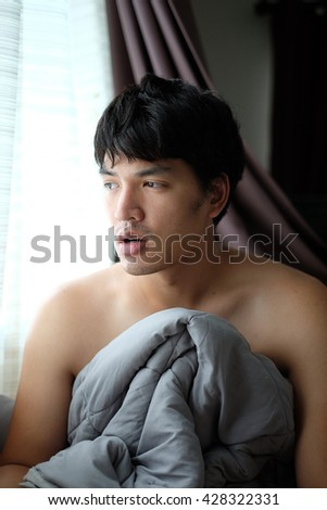 Shirtless Asian man wake up on the bed with blanket - Soft Focus