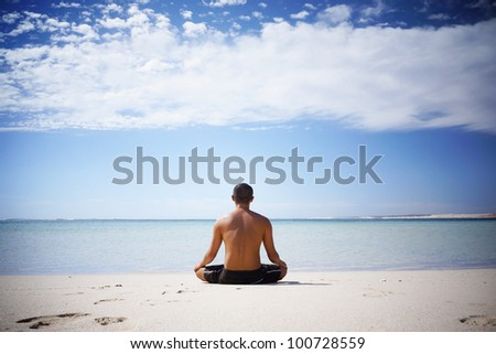 Shirtless Asian meditating by the ocean in Western Australia - stock photo
