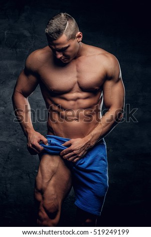 Shirtless athletic male in blue shorts showing his muscular leg.