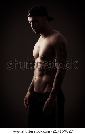 shirtless athletic muscular male model wearing cap posing side view color toned - stock photo