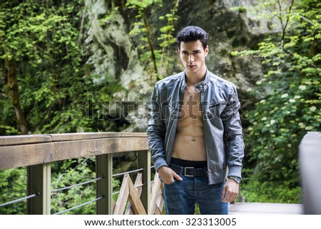 Shirtless Athletic Young Man Standing on Wooden Bridge on the River in the Woods, Wearing Leather Jacket on Naked Torso - stock photo