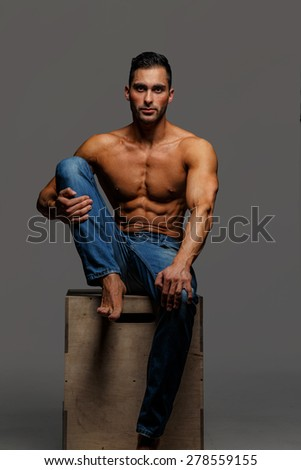 Shirtless attractive muscular guy in blue jeans sitting on podium on grey background - stock photo