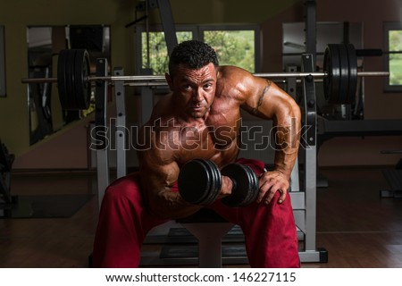 shirtless body builder doing heavy weight exercise for biceps - stock photo