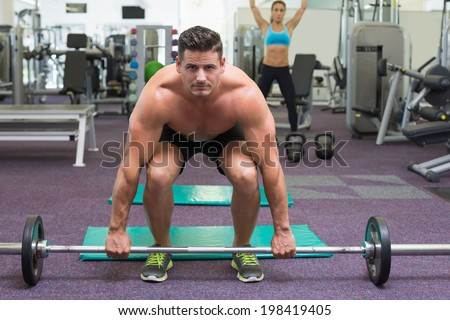 Shirtless bodybuilder about to lift heavy barbell at the gym - stock photo