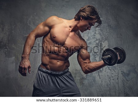 Shirtless bodybuilder doing exercises on biceps over grey wall.