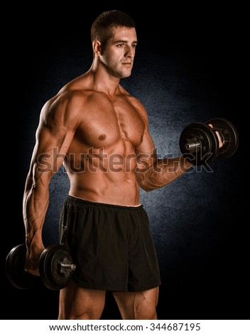 Shirtless bodybuilder holding dumbell and showing his muscular
