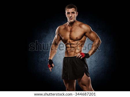 Shirtless bodybuilder holding dumbell and showing his muscular  - stock photo