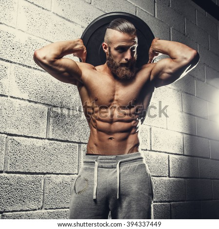 Shirtless bodybuilder holds lifting weight. - stock photo