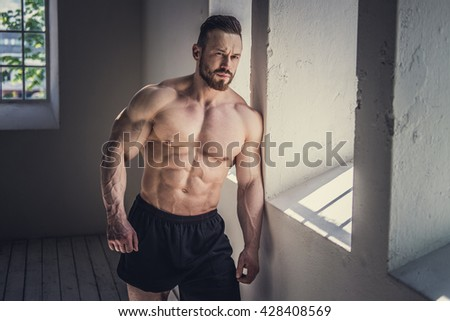 Shirtless bodybuilder posing in natural light.