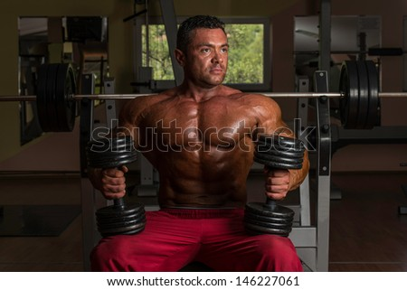 shirtless bodybuilder posing with dumbbell at the bench