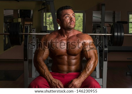 shirtless bodybuilder resting at the bench
