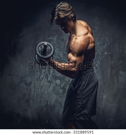 Shirtless bodybuilder showing his great body and holding dumbell. - stock photo
