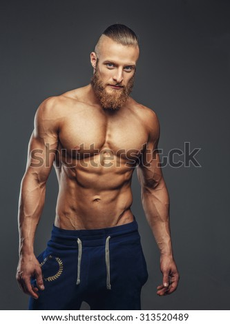Shirtless bodybuilder with beard posing. Isolated on grey background.