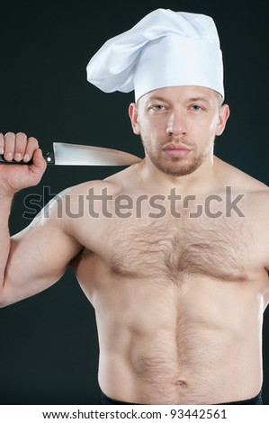 Shirtless caucasian chef holding a kitchen knife over dark background - stock photo