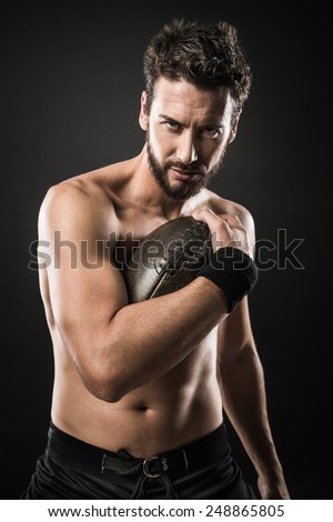 Shirtless confident football player holding ball and showing his muscular body - stock photo