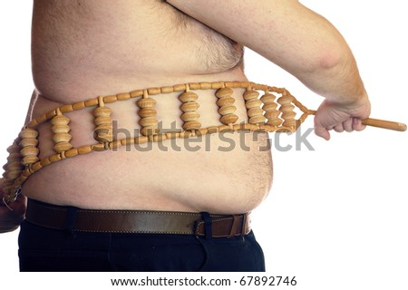shirtless fat man with a wooden massager - stock photo