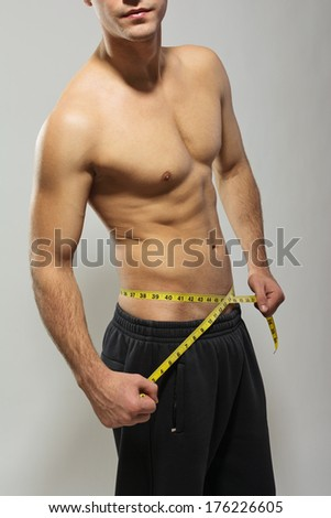 Shirtless fit handsome young Caucasian man measuring his waist using measure tape against gray background. Fitness, weight loss, healthy lifestyle concept.  - stock photo