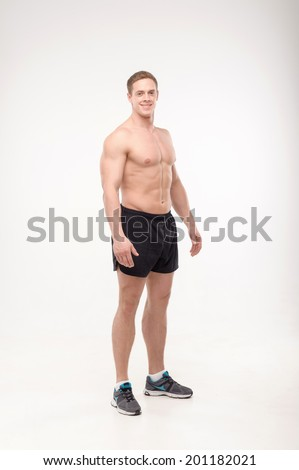 Shirtless healthy athletic smiling young man side view portrait, isolated on white background - stock photo